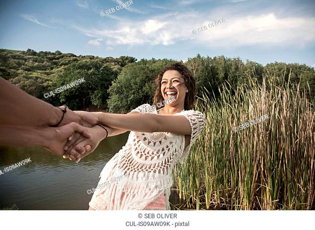 Young woman by river holding hands, leaning back smiling