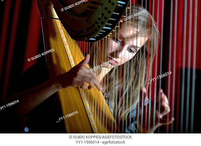 Young, female student at conservatoire playing harp at graduate level