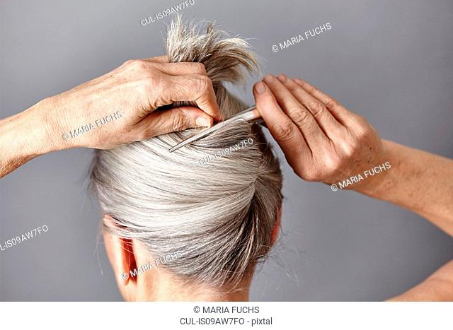 Rear view of woman styling gray hair into bun