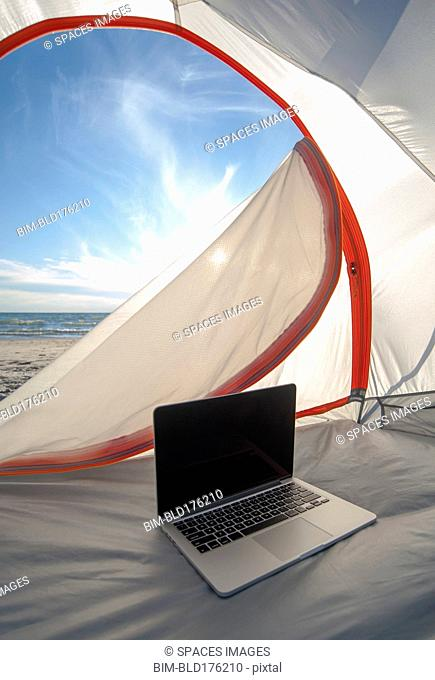 Laptop in camping tent on beach