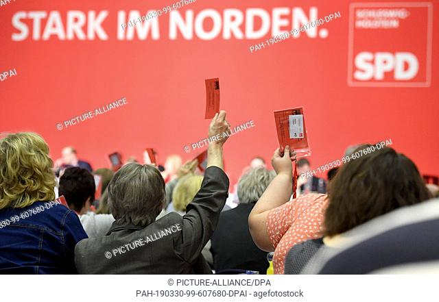 30 March 2019, Schleswig-Holstein, Norderstedt: Delegates lift their voting cards at the SPD Schleswig-Holstein state party conference
