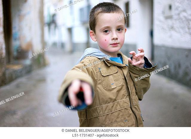 Boy adopting martial art posture on the street, Ludiente, Castellón, Spain