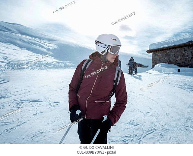 Young female skier wearing helmet and ski goggles looking back in snowy landscape, Alpe Ciamporino, Piemonte, Italy