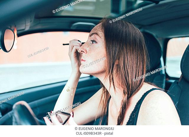 Young woman with freckles applying eyeshadow in car mirror