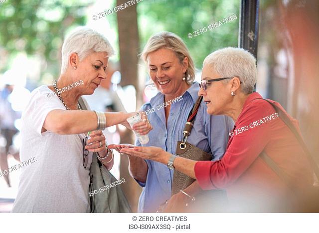 Senior and mature women sharing hand cream in city