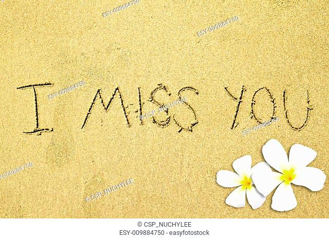 handwritten i miss you with frangipani flower on sand