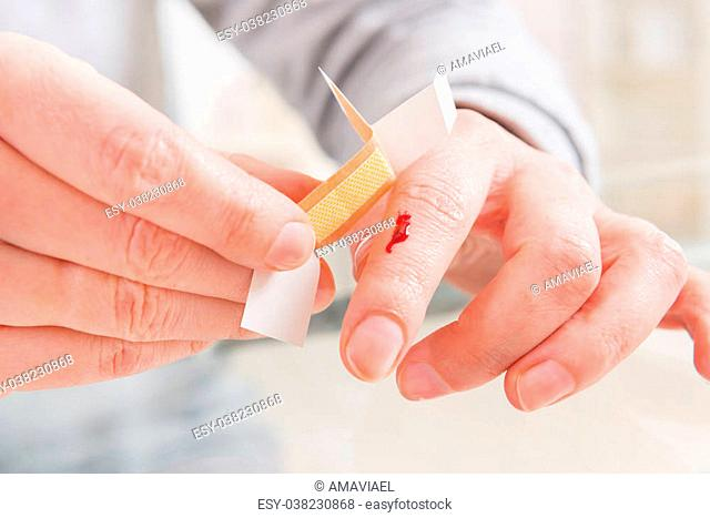 Applying adhesive bandage on bleeding finger