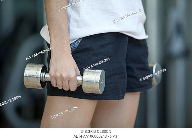 Woman lifting dumbbells, cropped