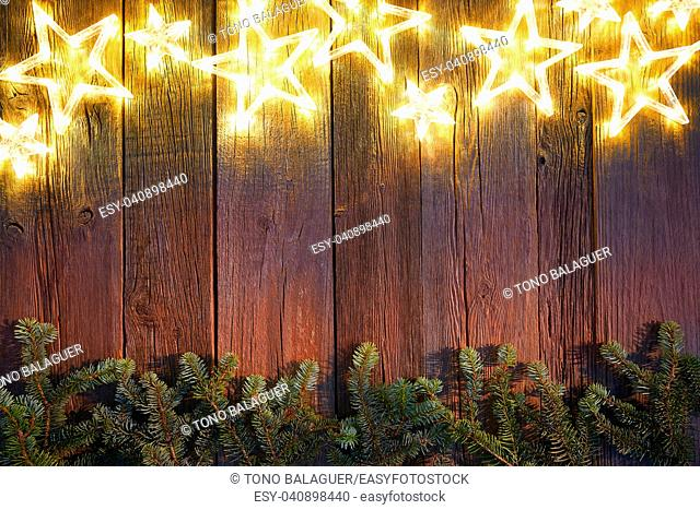 Christmas glowing stars and fir on vintage wooden background copy space