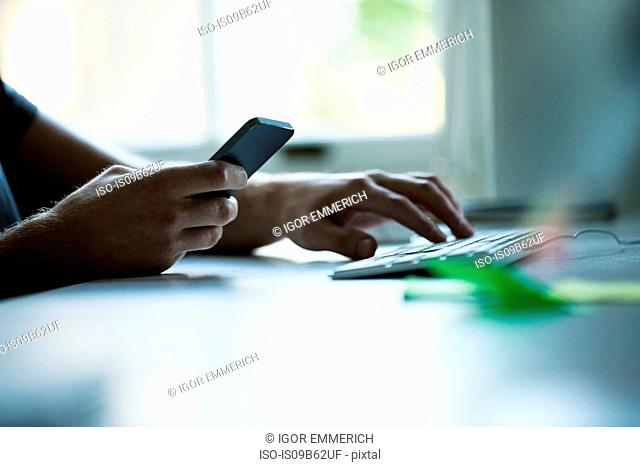 Hand of male designer using smartphone and typing on keyboard at creative studio desk