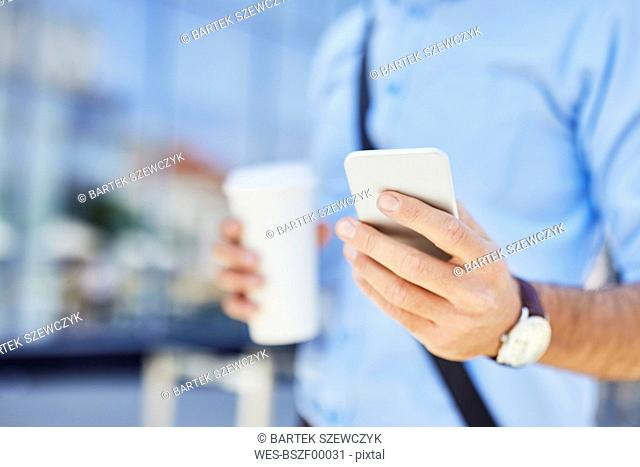 Close-up of businessman using smartphone outdoors