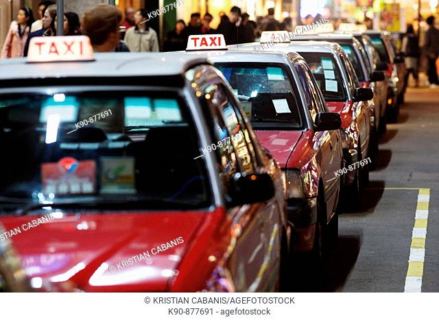 The typical red taxis queueing up idle at a taxi stand in Wanchai (Wan Chai) and waiting for customer, Hong Kong Island, Hong Kong, China, East Asia
