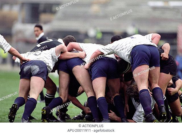 Rugby teams push against each others packs in scrum