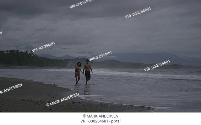 Slow motion wide tracking shot of couple walking on beach / Esterillos, Puntarenas, Costa Rica