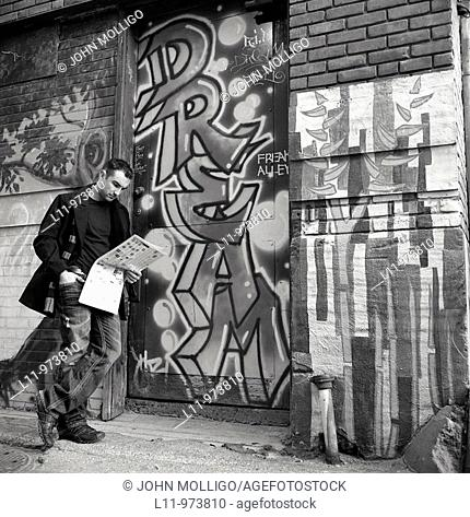 Man standing in alley reading newspaper