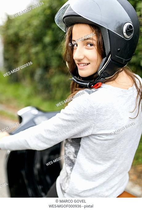 Portrait of smiling girl wearing motorcycle helmet sitting on a Vespa