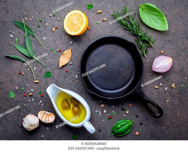 Empty old cast iron skille on dark stone background. Ingredients for making steak concept with copy space . Various herbs and seasoning rosemary ,sage