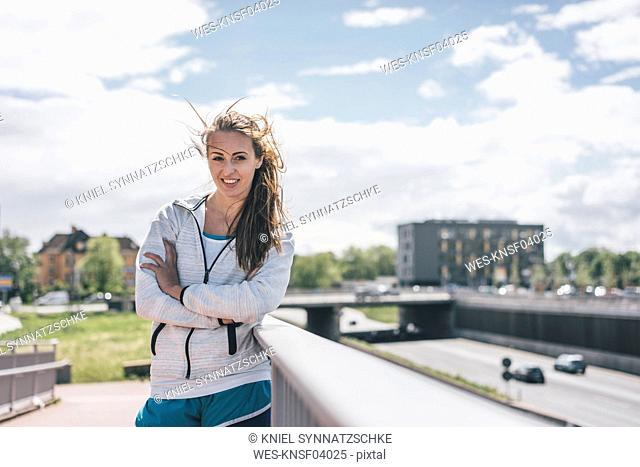 Portrait of smiling sportive young woman at motorway