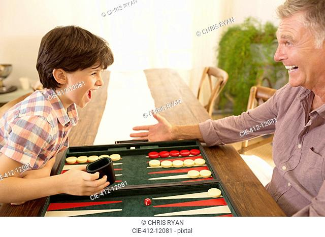 Grandfather and grandson playing backgammon