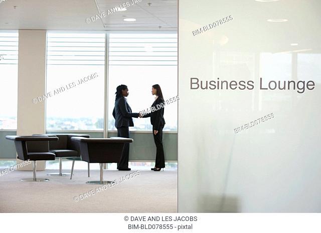 Businesswomen shaking hands in business lounge