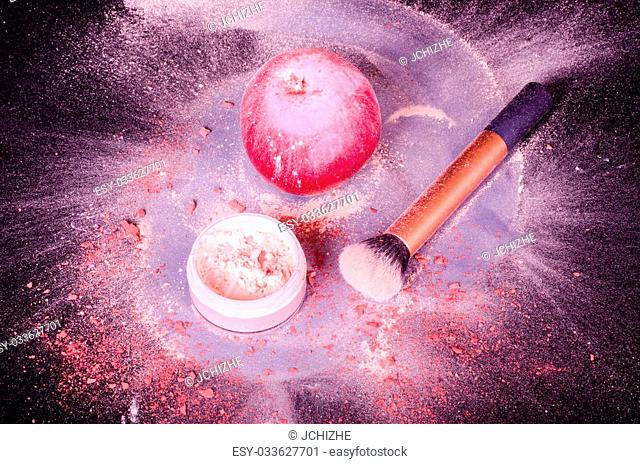 Face powder, brush, and red apple on black background