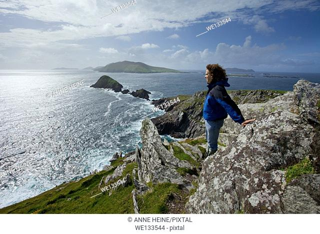 man on cliffs looking out on blasket islands, ireland