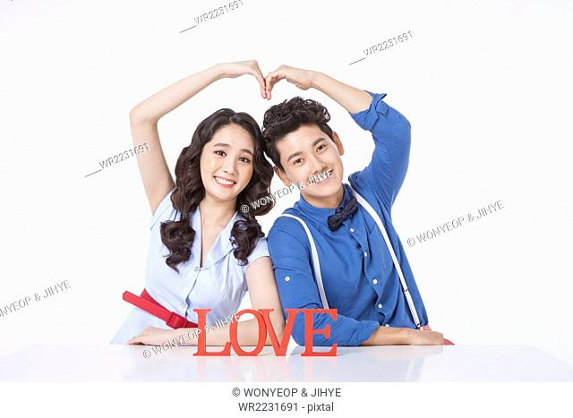 Young adult couple in retro style seated at table with solid word LOVE making a heart shape with their hands and staring forward with a smile