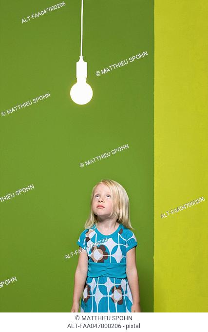 Little girl staring up at illuminated light bulb suspended overhead