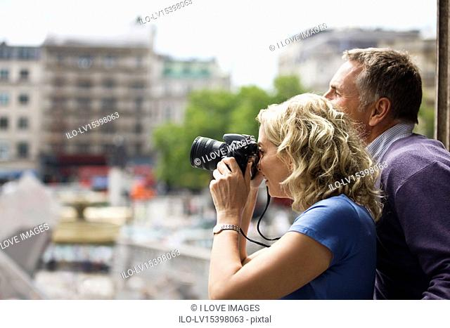 A middle-aged couple taking a photograph of Trafalgar square
