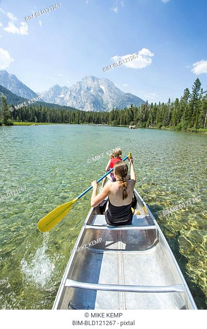 Caucasian mother and daughter paddling canoe on lake