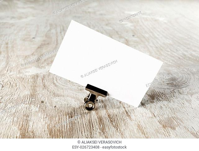 Photo of blank business card with soft shadow on light wooden background. Mock-up for branding identity. Blank template for your design
