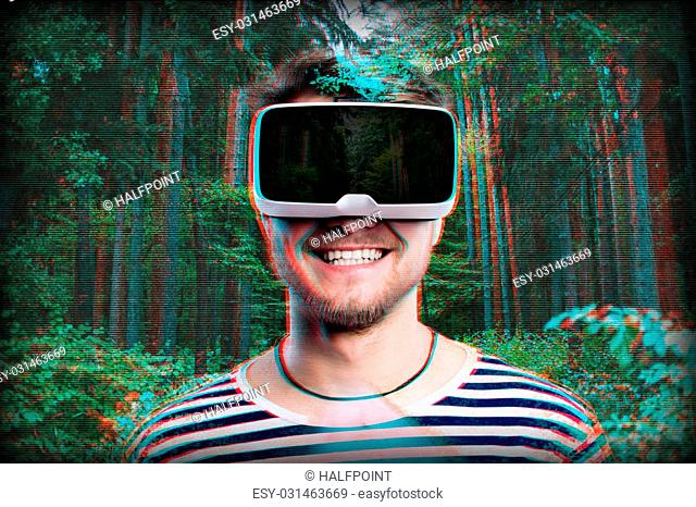 Hipster man in striped black and white sweatshirt wearing virtual reality goggles. Green forest