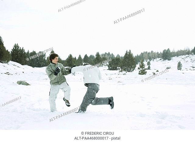 Two young male friends roughhousing in snow, full length