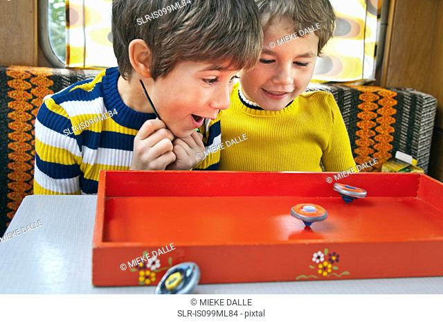 Two boys playing with spinning tops in caravan