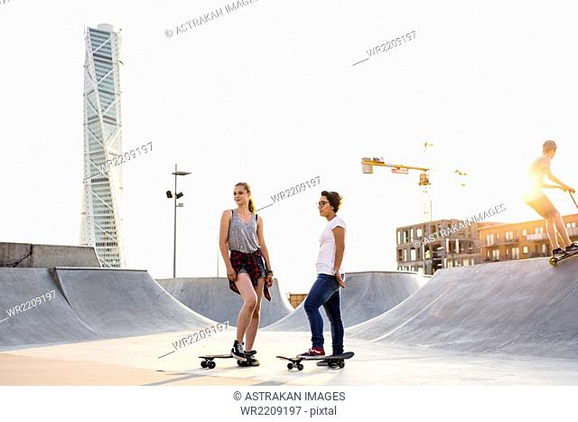 Full length of teenage girls with skateboards at skate park with Turning Torso in background