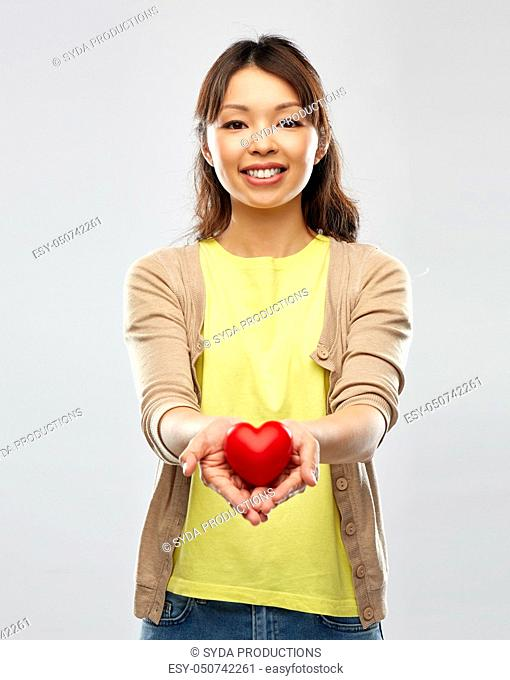 happy asian woman holding red heart
