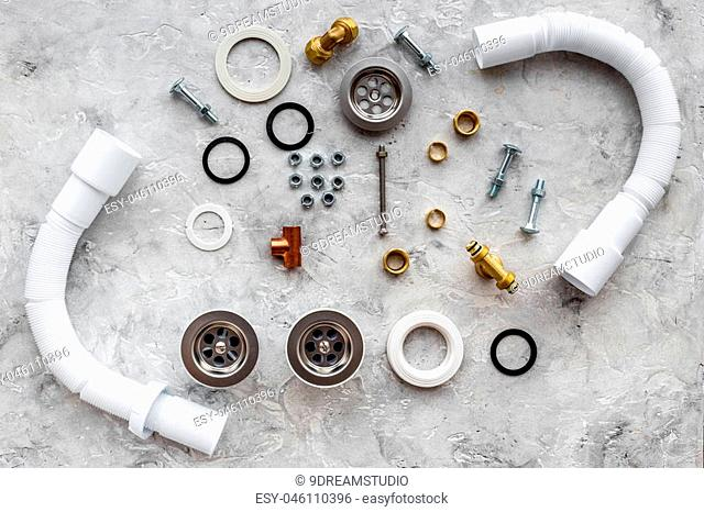 Drain parts and plumbing tools on grey stone background top view