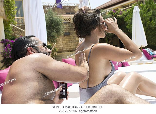 Man rubbing sunscreen on his woman's back by the pool