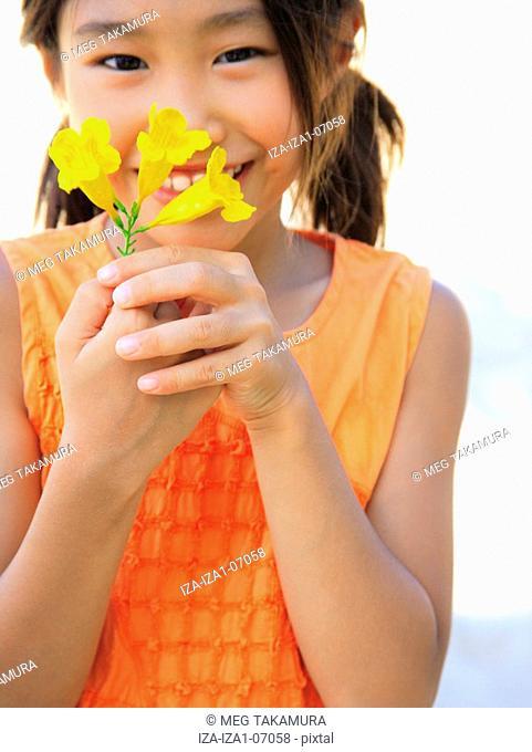 Portrait of a girl smelling Allamanda flowers