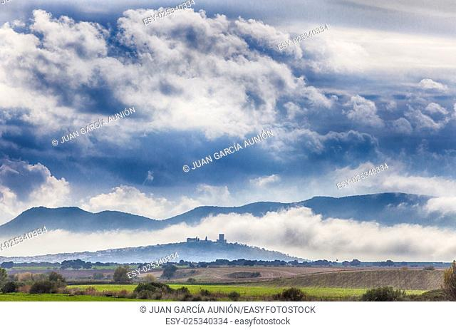 Early afternoon scenery of cereals fields and little town with castle between the fog, Nogales, Spain