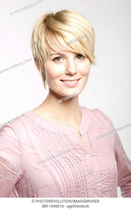 Young blond woman with short hair smiling into the camera in a friendly way