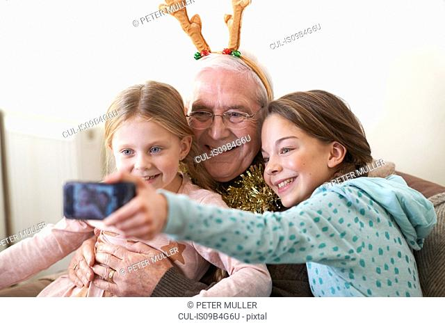 Sisters taking smartphone selfie with grandfather in reindeer antlers