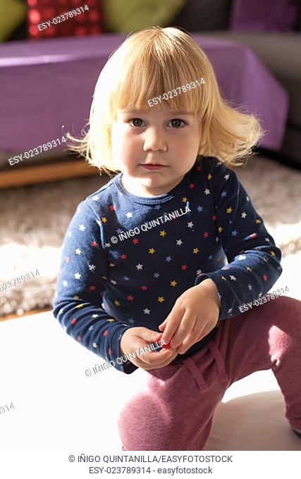 portrait of caucasian baby two years old age with fringe or bang and long blonde hair chubby face looking at camera serious expression wearing a blue shirt pink...