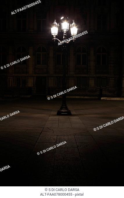 Street lamp illuminated at night in Place de l'Hotel de Ville, Paris, France