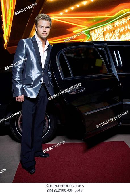 German man standing by limousine outside nightclub