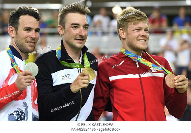 Flanked by silver medalist Mark Cavendish (L) of Great Britain and Lasse Norman Hansen (R) of Denmark, Elia Viviani of Italy celebrates with his gold medal...
