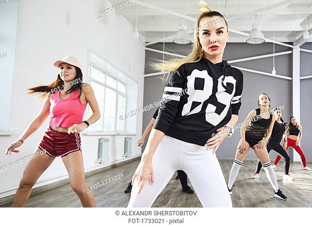 Confident young female in sports clothing dancing at studio