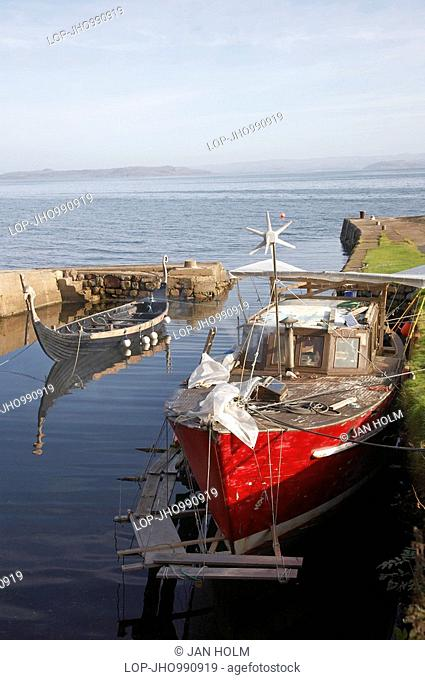 Scotland, North Ayrshire, Corrie, A fishing boat and replica Viking boat in Corrie Harbour on the Isle of Arran