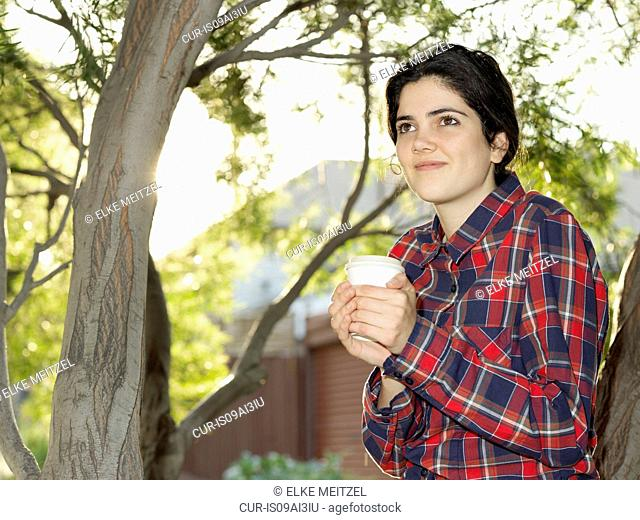 Portrait of smiling young woman with takeaway coffee