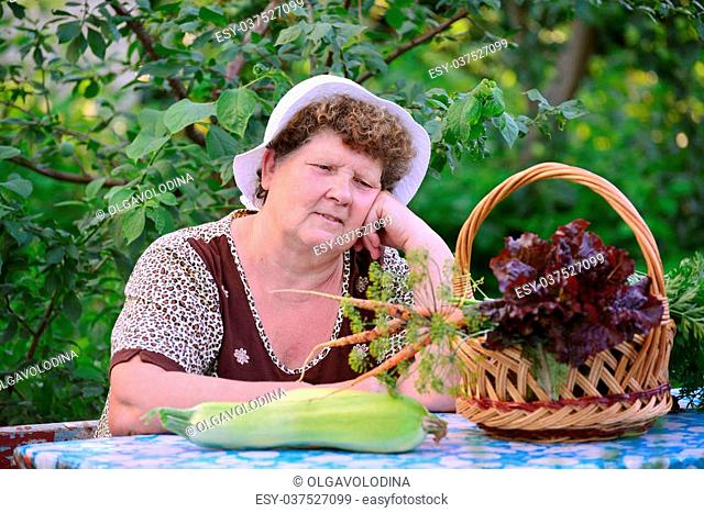 elderly woman with a basket of vegetables sitting at the table